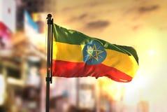 反对城市被弄脏的背景的埃塞俄比亚旗子在日出Backlig 皇族释放例证