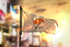 反对城市被弄脏的背景的塞浦路斯旗子在日出背后照明 库存图片