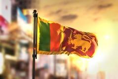 反对城市被弄脏的背景的斯里兰卡旗子在日出Backli 免版税库存图片