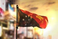 反对城市被弄脏的背景的巴布亚新几内亚旗子在日出 图库摄影
