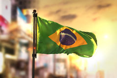 反对城市被弄脏的背景的巴西旗子在日出背后照明 免版税库存照片