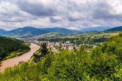 反对多云天空的一个别致的山风景和一个绿色森林和一个小镇谷的 库存图片