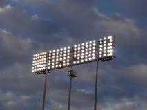 反对多云天空的体育场式光 免版税库存图片