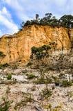 反对多云天空的剧烈的黄色砂岩峭壁 免版税库存照片