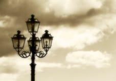 反对多云天空的古老路灯柱,葡萄酒 免版税库存图片
