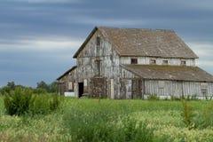 反对多云天空的老腐朽的谷仓 库存图片