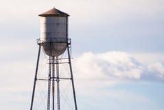 反对多云天空的老被放弃的水塔 免版税图库摄影