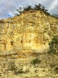 反对多云天空的黄色砂岩峭壁 库存照片