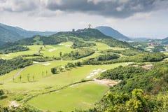 反对多云天空的绿色高尔夫球领域 免版税库存图片
