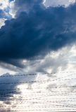 反对多云天空背景的铁丝网 库存图片