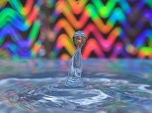 反对多彩多姿的背景的水飞溅 免版税库存图片