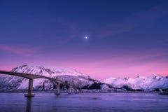 反对多雪的山、紫色天空与桃红色云彩和月亮的桥梁 免版税图库摄影