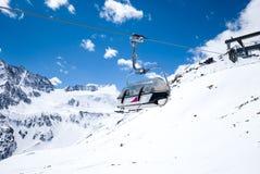 反对多雪的山的驾空滑车位子 库存图片
