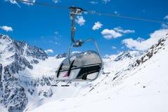 反对多雪的山的驾空滑车位子 免版税库存照片
