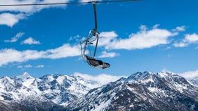 反对多雪的山的驾空滑车 免版税库存照片