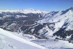 反对多雪的山脉的高山滑雪胜地谷 免版税图库摄影