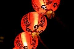 反对夜空的三个橙色中国灯笼 免版税库存图片