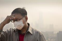 反对大气污染的人佩带的嘴面具 库存图片