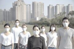 年轻反对大气污染的小组佩带的嘴面具在城市 库存照片