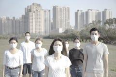 年轻反对大气污染的小组佩带的嘴面具在城市 免版税库存图片