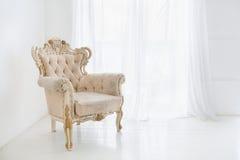 反对大窗口的葡萄酒古色古香的扶手椅子 图库摄影