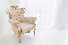 反对大窗口的葡萄酒古色古香的扶手椅子 免版税库存图片