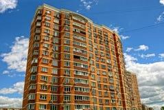 反对天空和云彩的一个多层的棕色砖房子 免版税库存图片