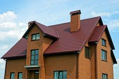 反对天空和云彩的现代棕色砖房子 库存照片