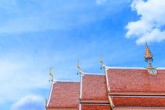 反对天空的一个金黄和橙色泰国教会屋顶 免版税库存照片