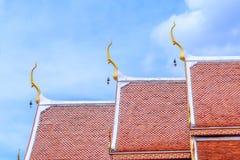 反对天空的一个金黄和橙色泰国教会屋顶 免版税图库摄影