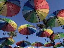 反对天空的多彩多姿的伞在背后照明 免版税库存图片