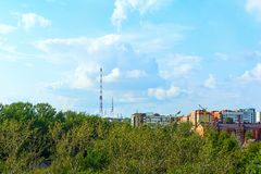 反对天空的电视塔和在城市旁边的森林 免版税库存照片
