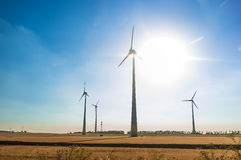 反对天空的风轮机与太阳 库存照片