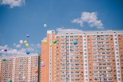 反对天空蔚蓝、云彩和居民住房的气球 最后呼叫和毕业在学校 库存图片