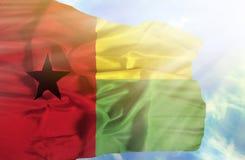 反对天空蔚蓝的几内亚比绍挥动的旗子与阳光 图库摄影
