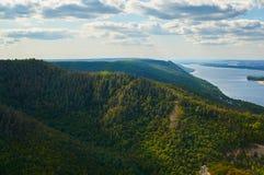 反对天空蔚蓝的河与云彩和森林 库存图片