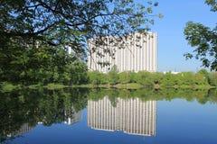 反对天空蔚蓝的现代白色多层的大厦与反射在池塘在早期的春天早晨在莫斯科俄罗斯 免版税库存照片