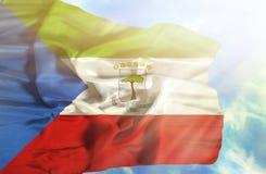 反对天空蔚蓝的赤道几内亚挥动的旗子与阳光 库存照片