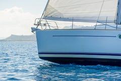 反对太阳的接近的看法在与被卷扬的前桅前方的帆的风船弓 图库摄影