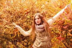反对室外秋季的叶子的奥秘妇女 免版税库存照片