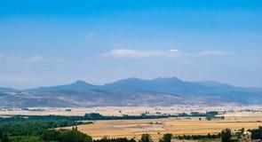 反对小山和山的干燥农村领域 免版税库存照片