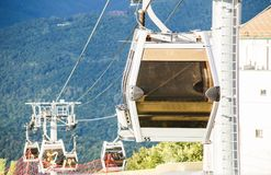 反对山坡背景的缆车客舱照片  免版税库存图片