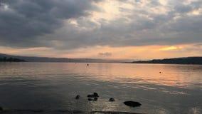 反对山的背景的日落在湖的在城市 股票视频