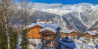 反对山的背景的积雪的村庄 山区度假村`劳拉,俄罗斯天然气工业股份公司` 索契, 2016年1月31日的俄罗斯 免版税库存照片