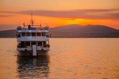 反对山背景的海洋小船在日落的 免版税库存照片