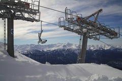 反对山脉全景的滑雪电缆车  免版税图库摄影