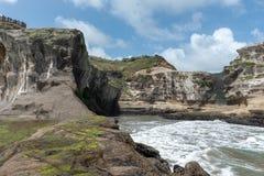 反对峭壁住房gannet殖民地的风大浪急的海面Muriwai海滩的 免版税库存图片