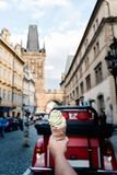 反对布拉格都市风景的年轻举行的trolo冰淇凌  免版税库存照片