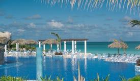 反对平静的海洋的热带游泳池和多云蓝天在晴天 免版税库存图片