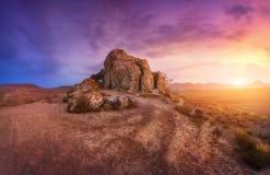 反对惊人的多云天空的岩石在日落的沙漠 免版税库存图片